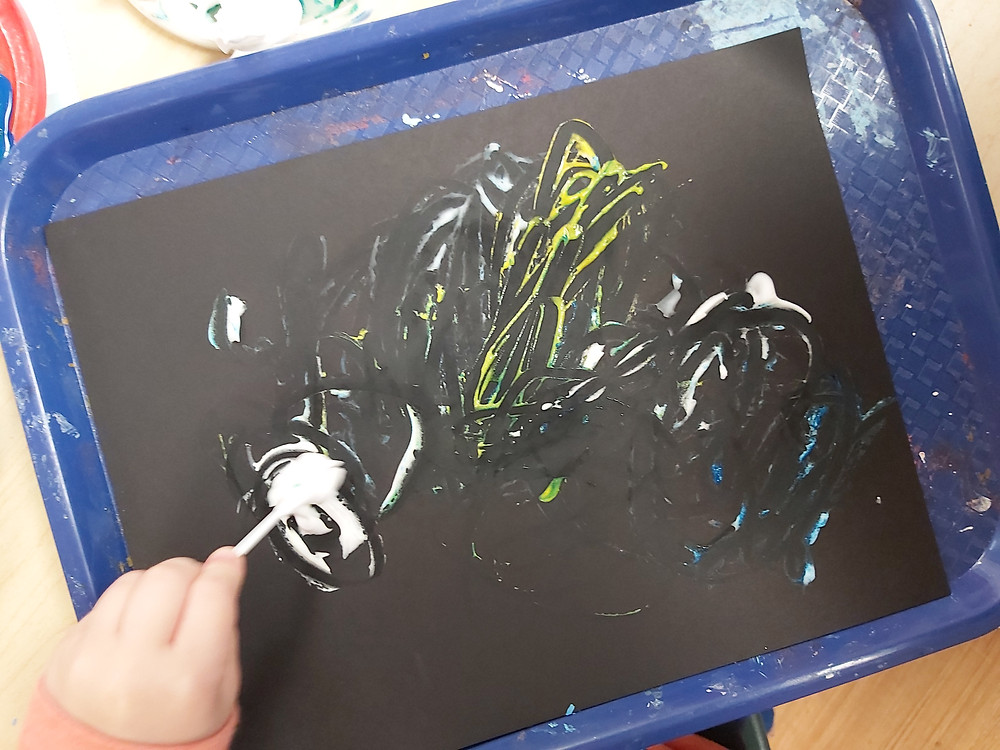 preschooler using eyeshadow applicator for hurrican art