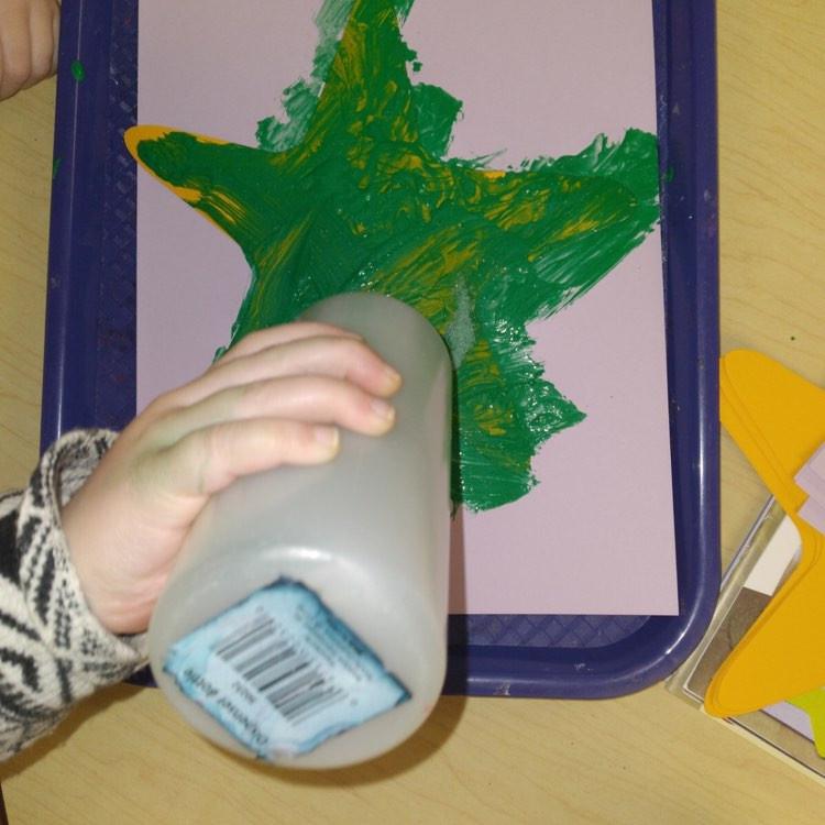 preschooler squeezing puffy paint onto starfish craft