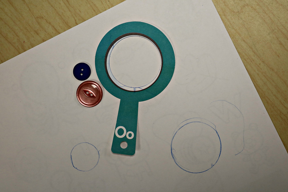 white paper with several traced circles, paper magnifying glass, and buttons