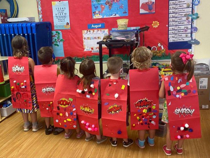 preschoolers lined up showing off superhero cape crafts
