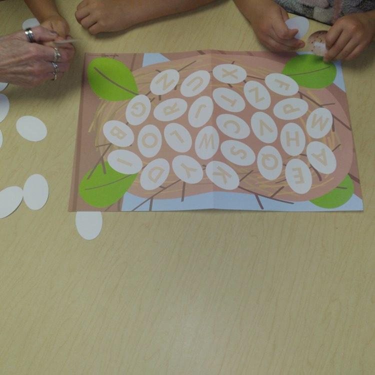 preschooler and teacher playing letter matching bird nest game