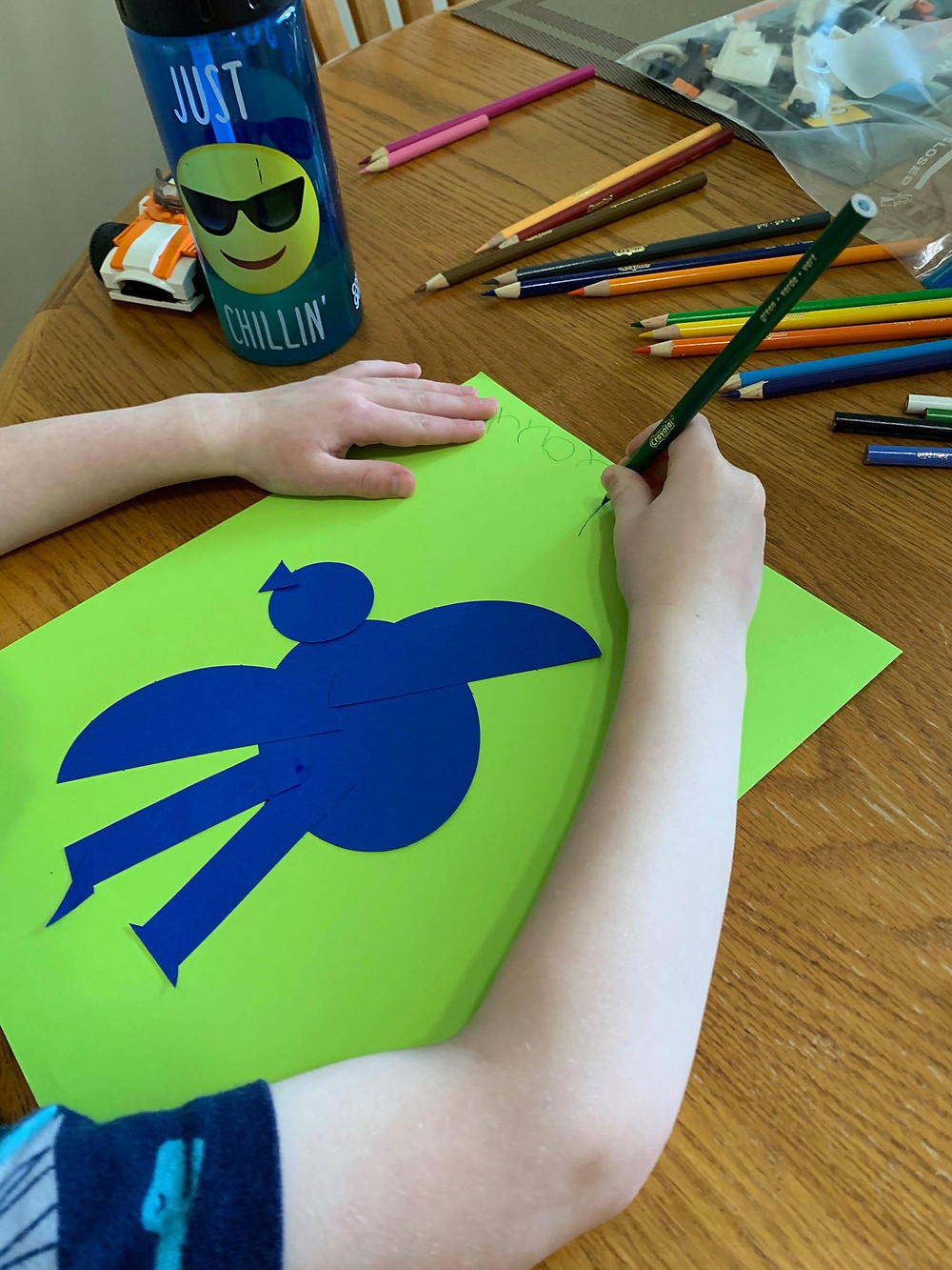 child making a bird collage using construction paper and colored pencils