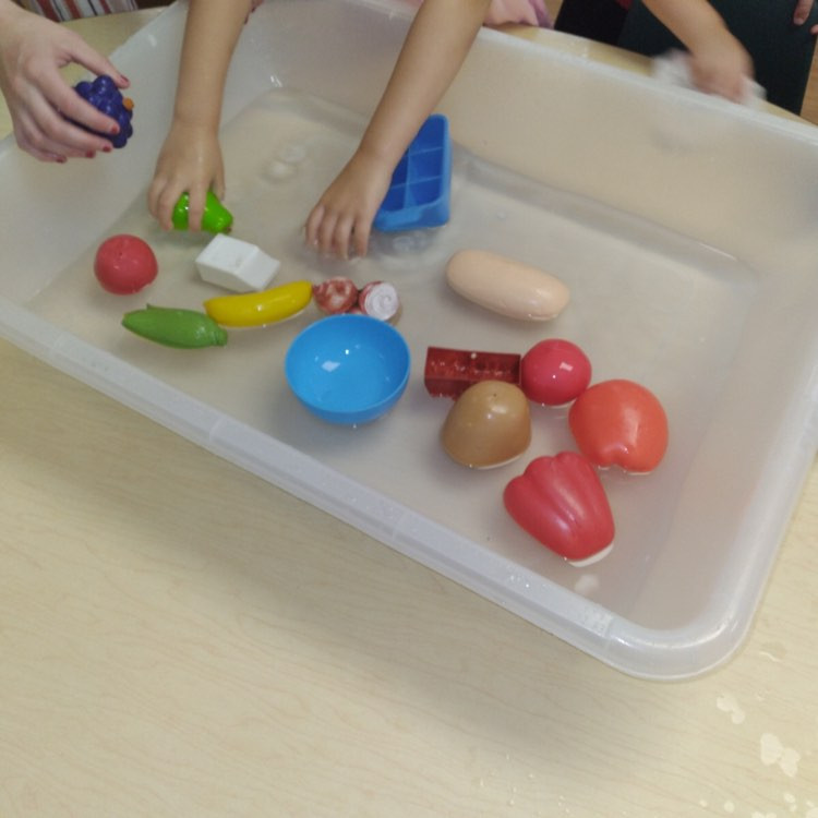 small group of preschoolers exploring water sensory bin filled with play kitchen food
