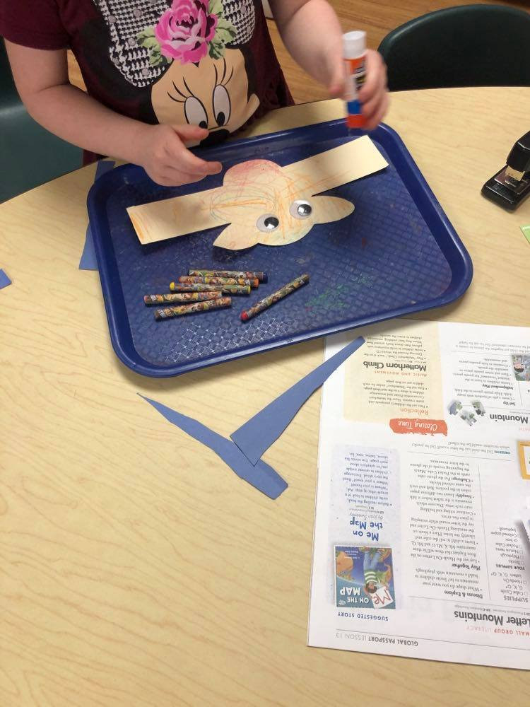 preschooler adding glue to mountain goat headband craft
