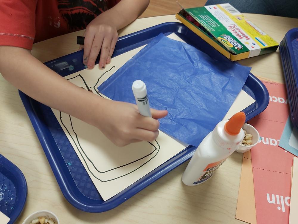 preschooler drawing river with marker