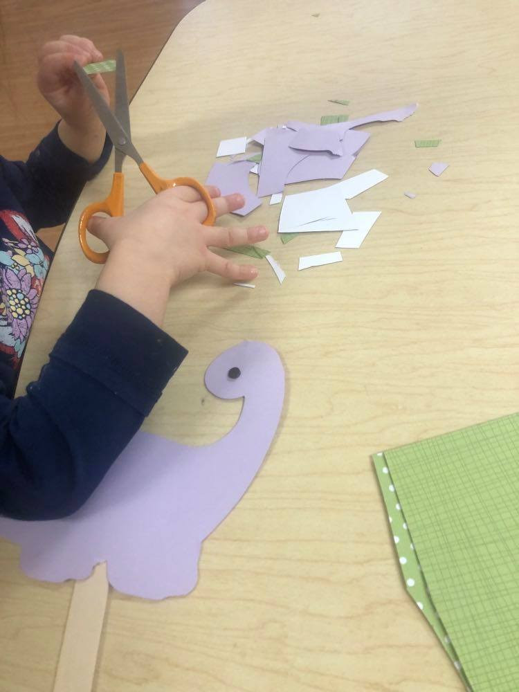 preschooler cutting paper to make Brontosaurus Puppet