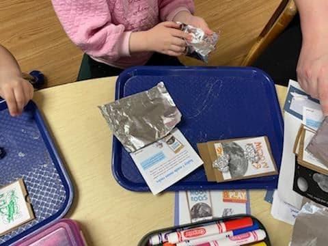 preschooler wrapping up a piece of aluminum foil