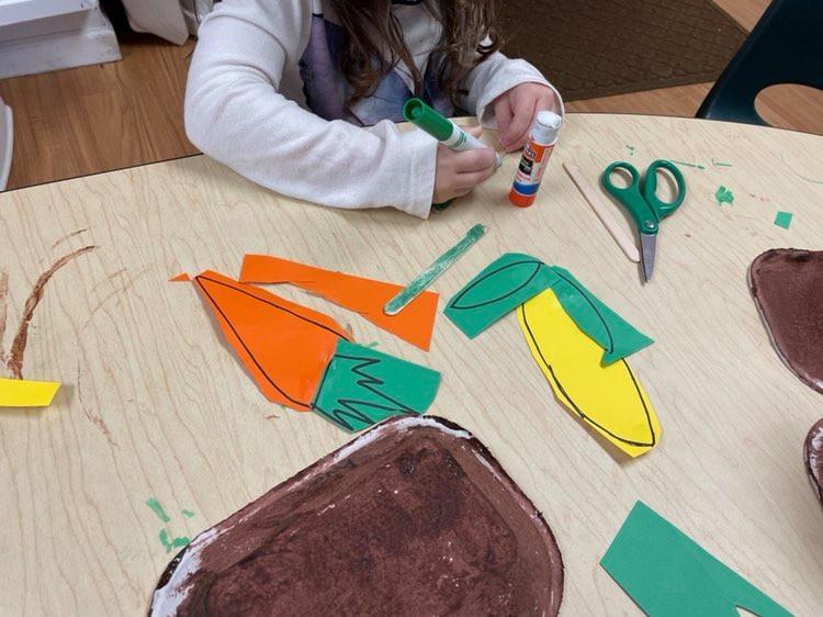 child coloring cardstock vegetable using marker