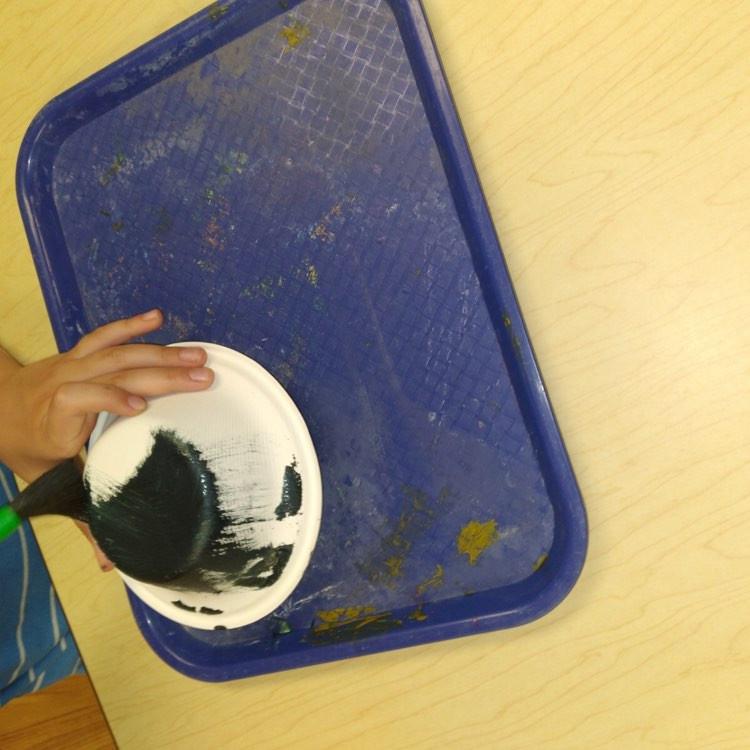 preschooler painting cardboard bowl