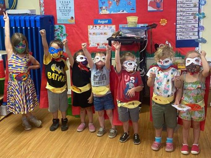 preschoolers lined up in superhero costumes