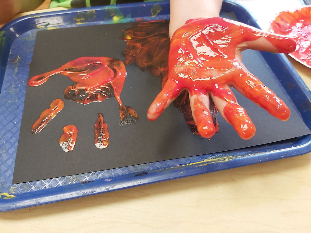 preschooler holding out painted hand