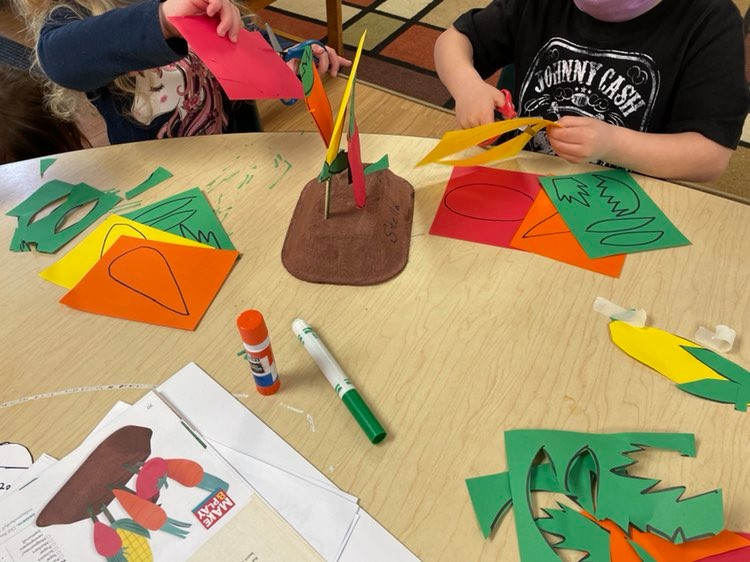 children cutting out vegetables shapes from cardstock