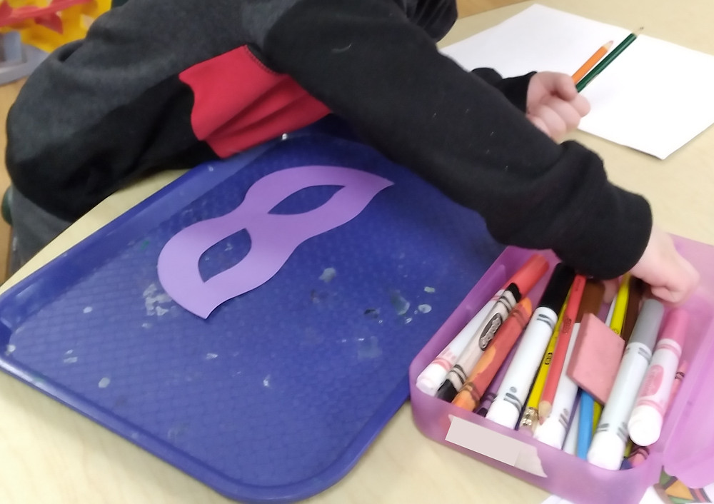 child reaching for colored pencils while creating paper mask