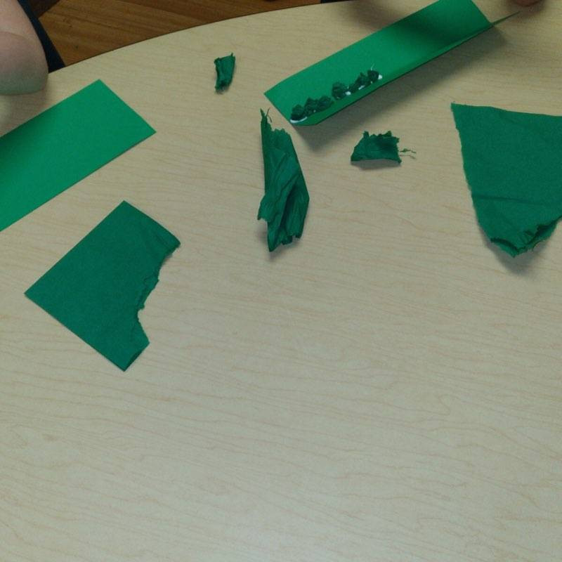 children lining up tissue paper peas on green paper pod
