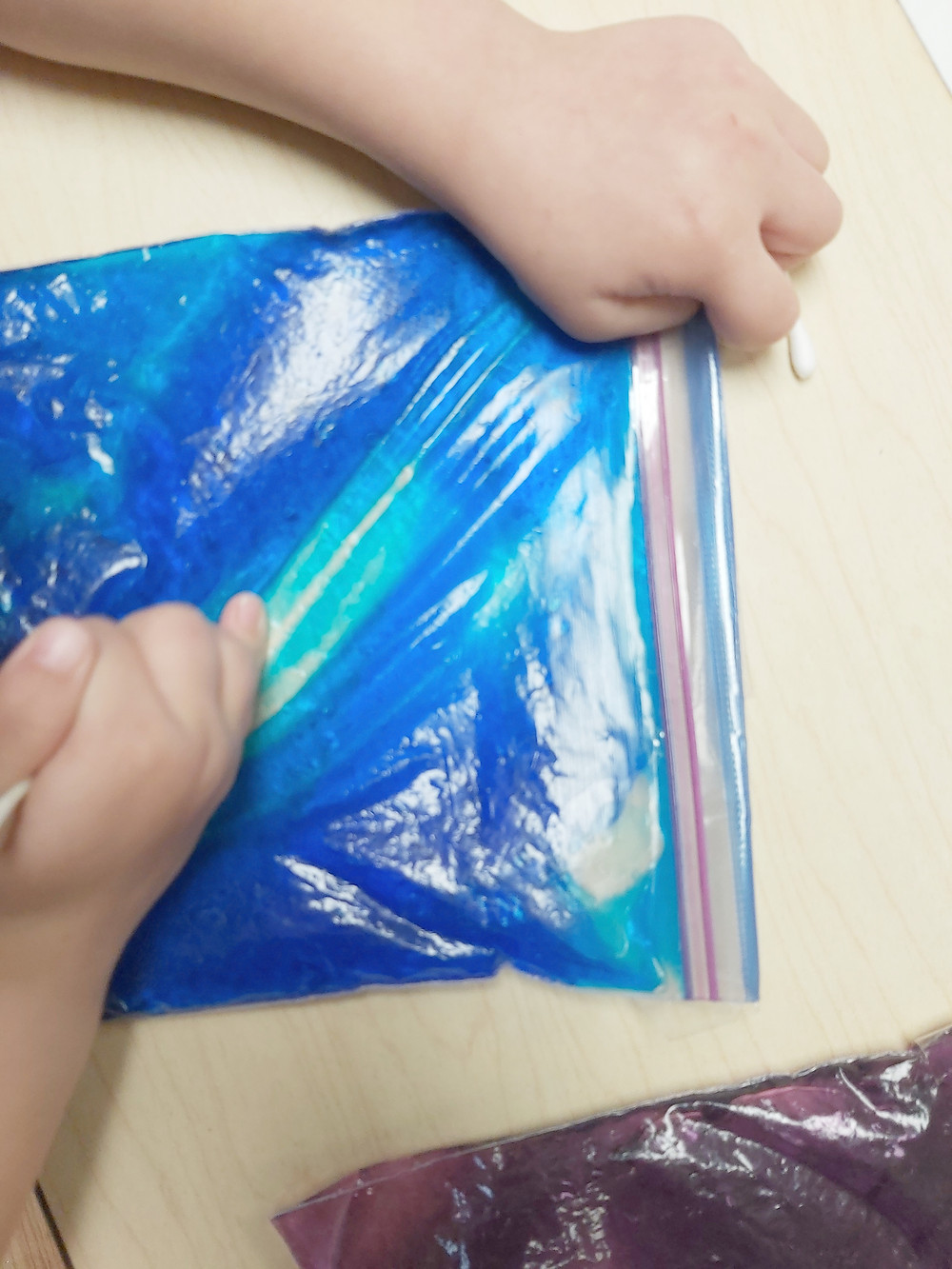 preschooler writing letters with q-tip