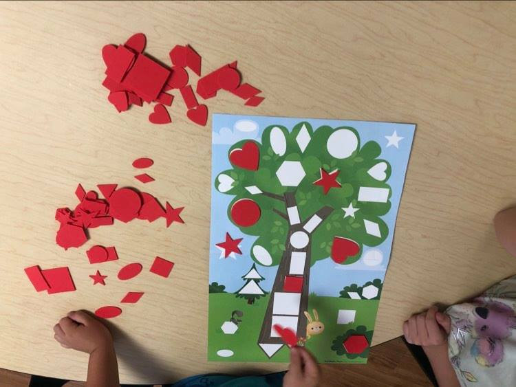 children matching red foam shapes to shape outlines on tree poster