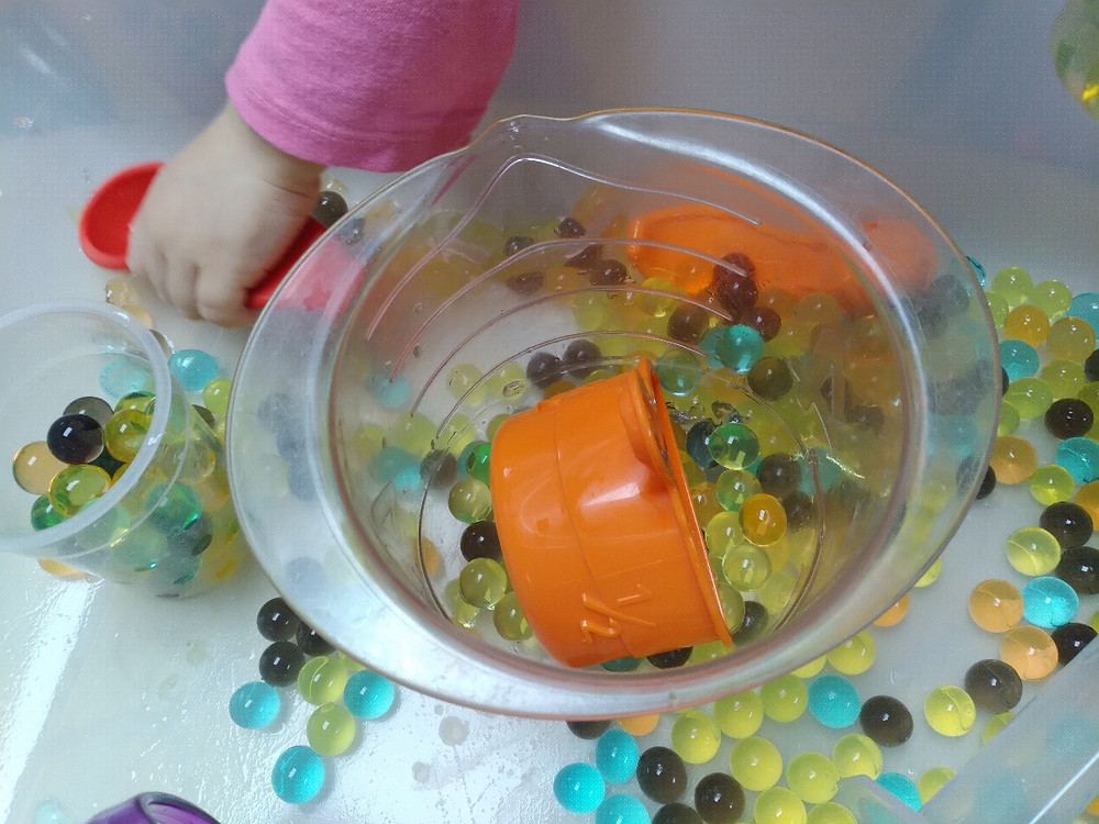 fall water bead sensory bin with measuring cups and spoons