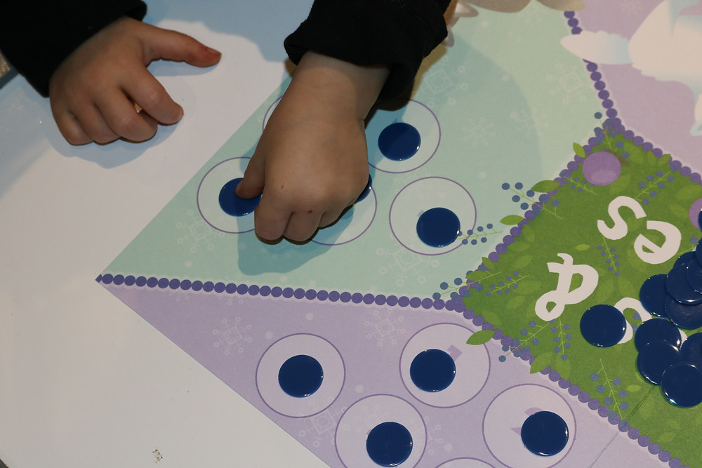 preschooler counting game pieces and adding to gameboard