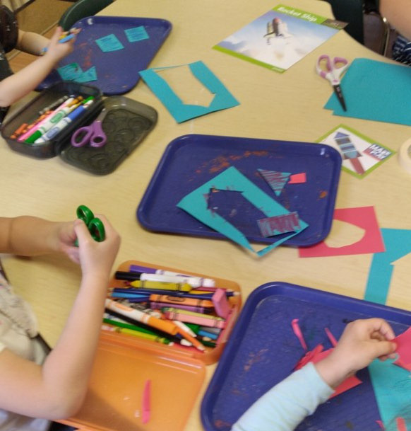 group of preschoolers making paper rocket ship crafts
