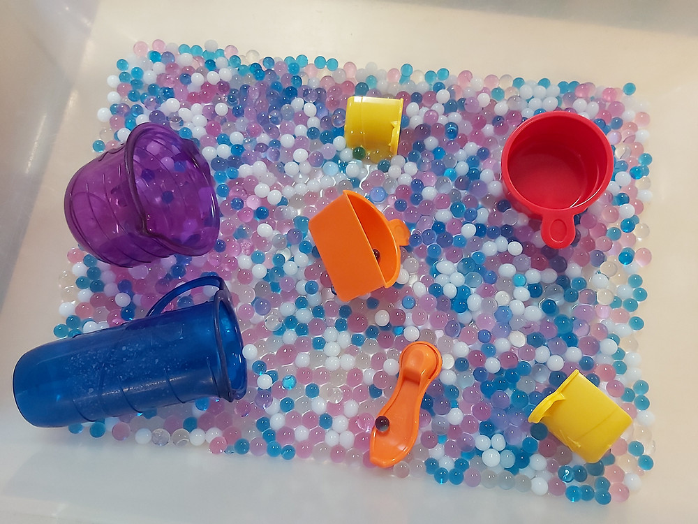 mixing and measuring water bead sensory bin