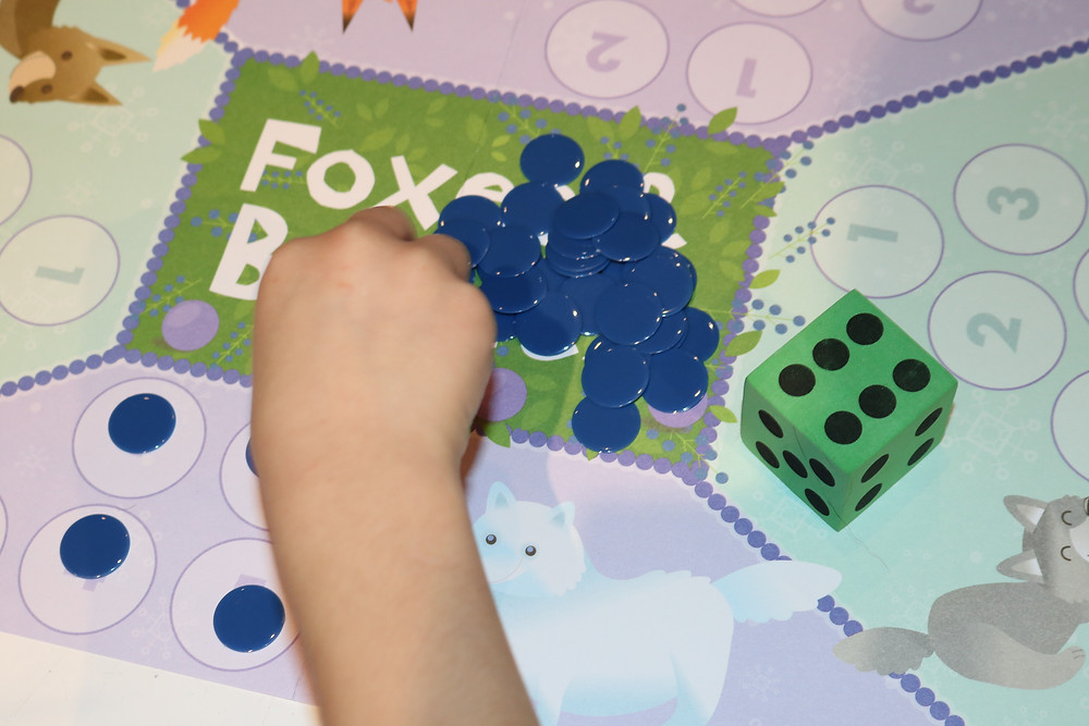 child counting game pieces and adding to gameboard