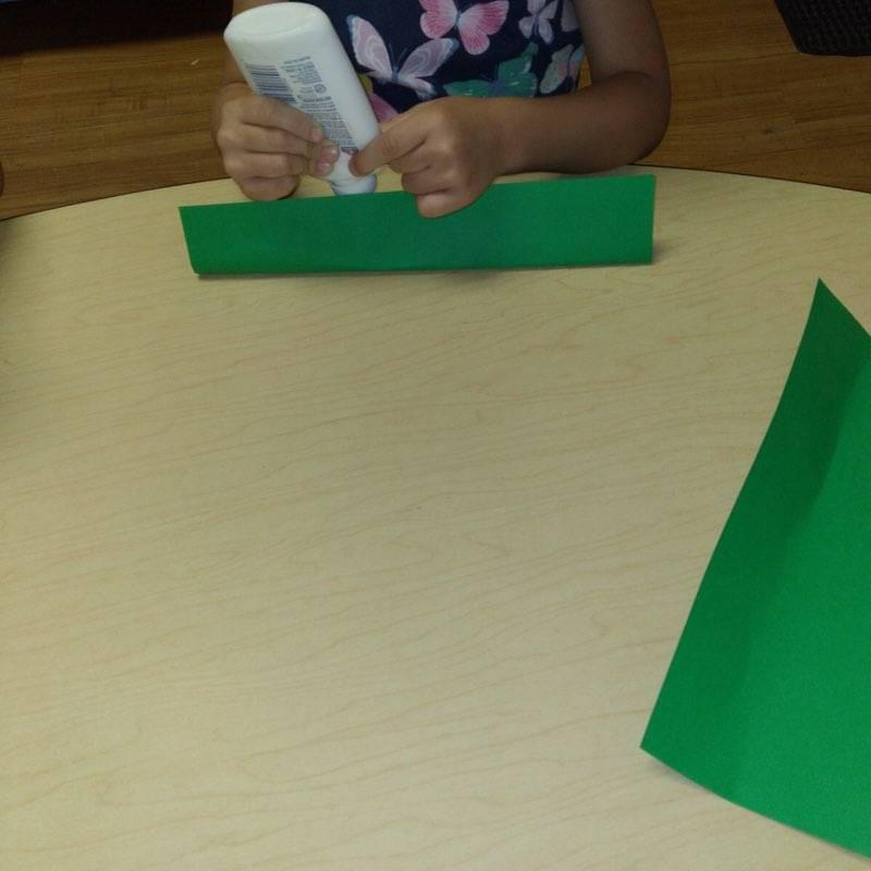preschooler squeezing glue onto green paper