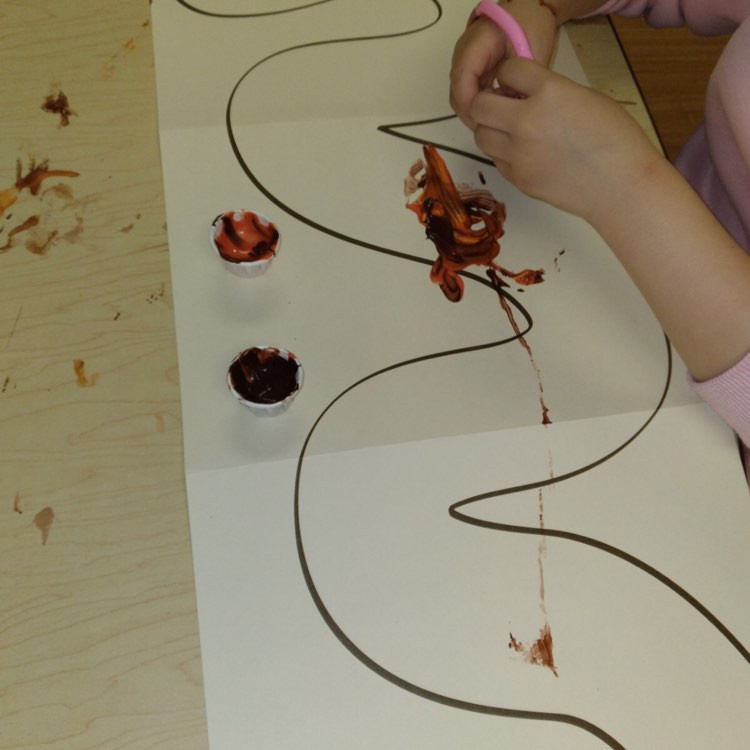 preschooler painting on worm outline with rubber worms