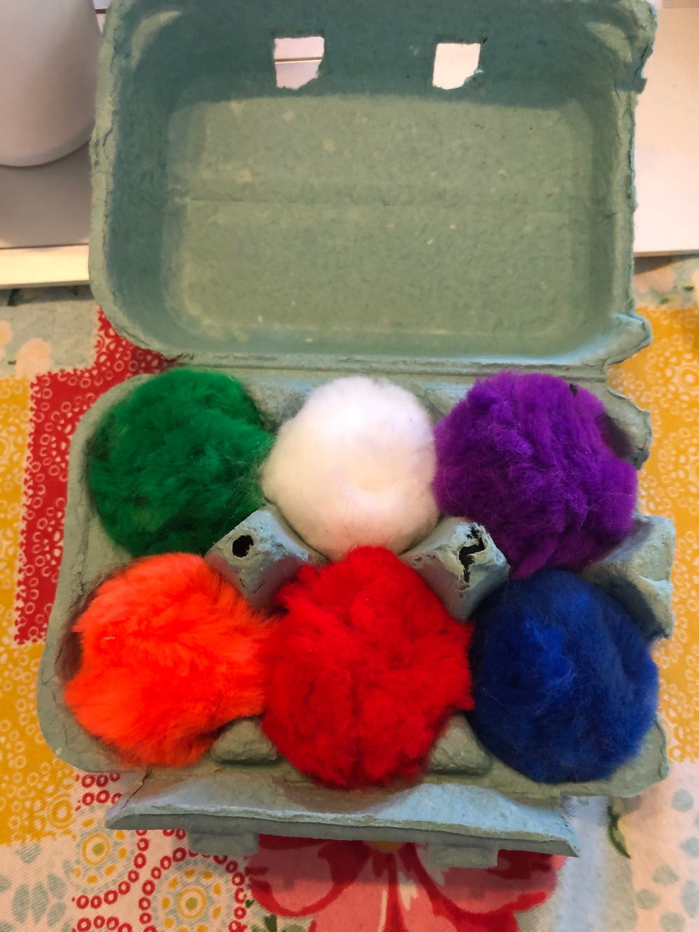 colored pompoms in half egg carton