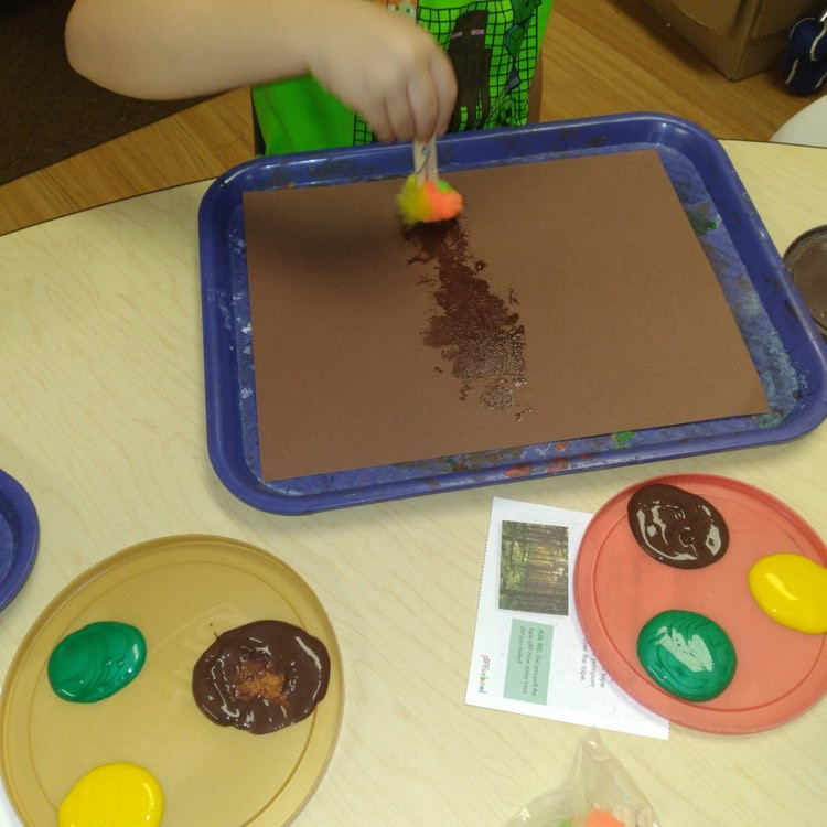 preschool using pompom to paint trees on brown cardstock