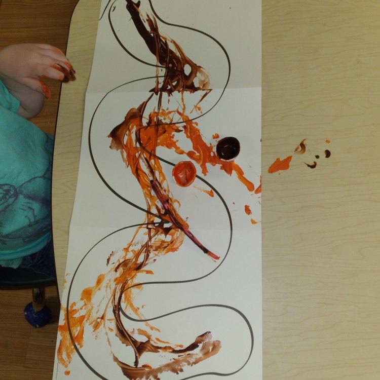 preschooler making worm art using paint