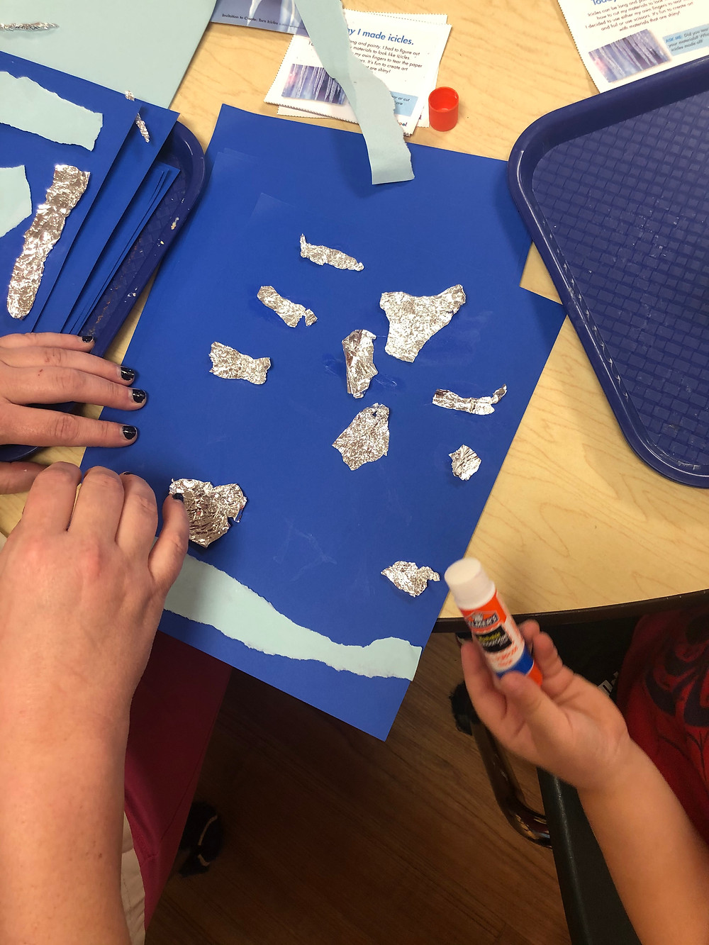 preschooler gluing foil to cardstock to make icicle art