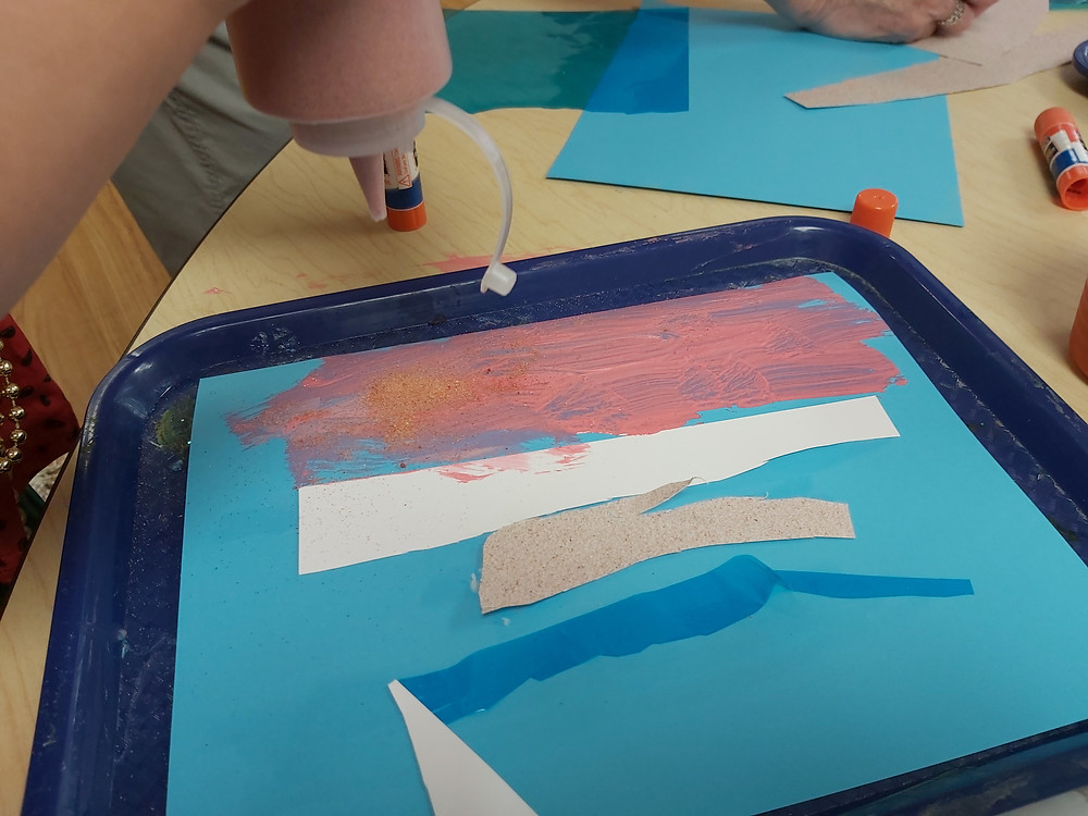 preschooler sprinkling sand on process art