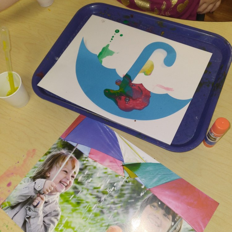 preschooler making umbrella craft with watery paint