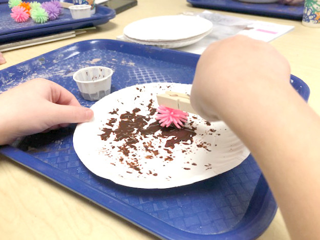 child painting on paper plate using pokey ball and clothepin