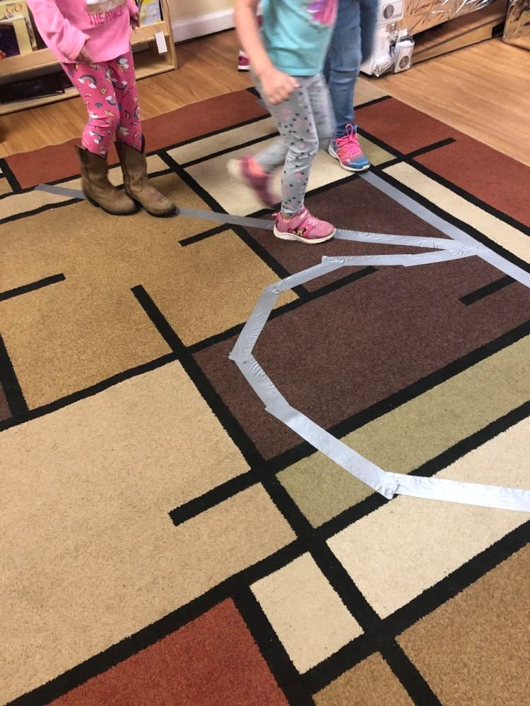 preschoolers walking along R made with tape on the floor