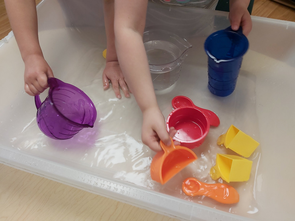 preschoolers playing in water with measuring cups