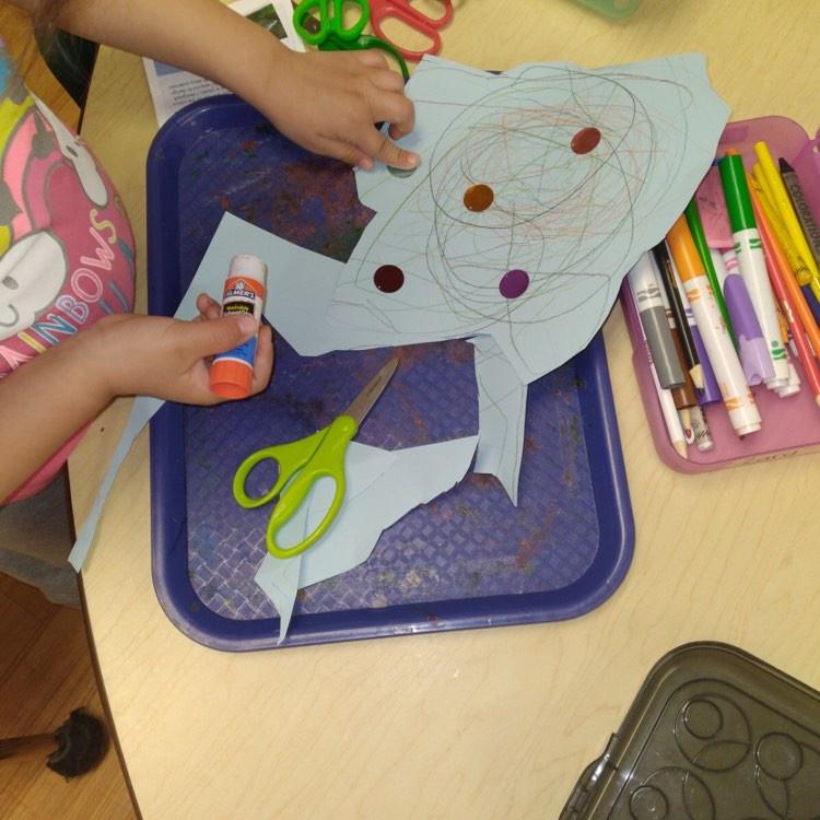 preschooler making rainbowfish art with sequins and glue