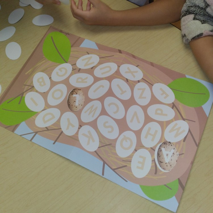 two children playing letter matching nest game on table