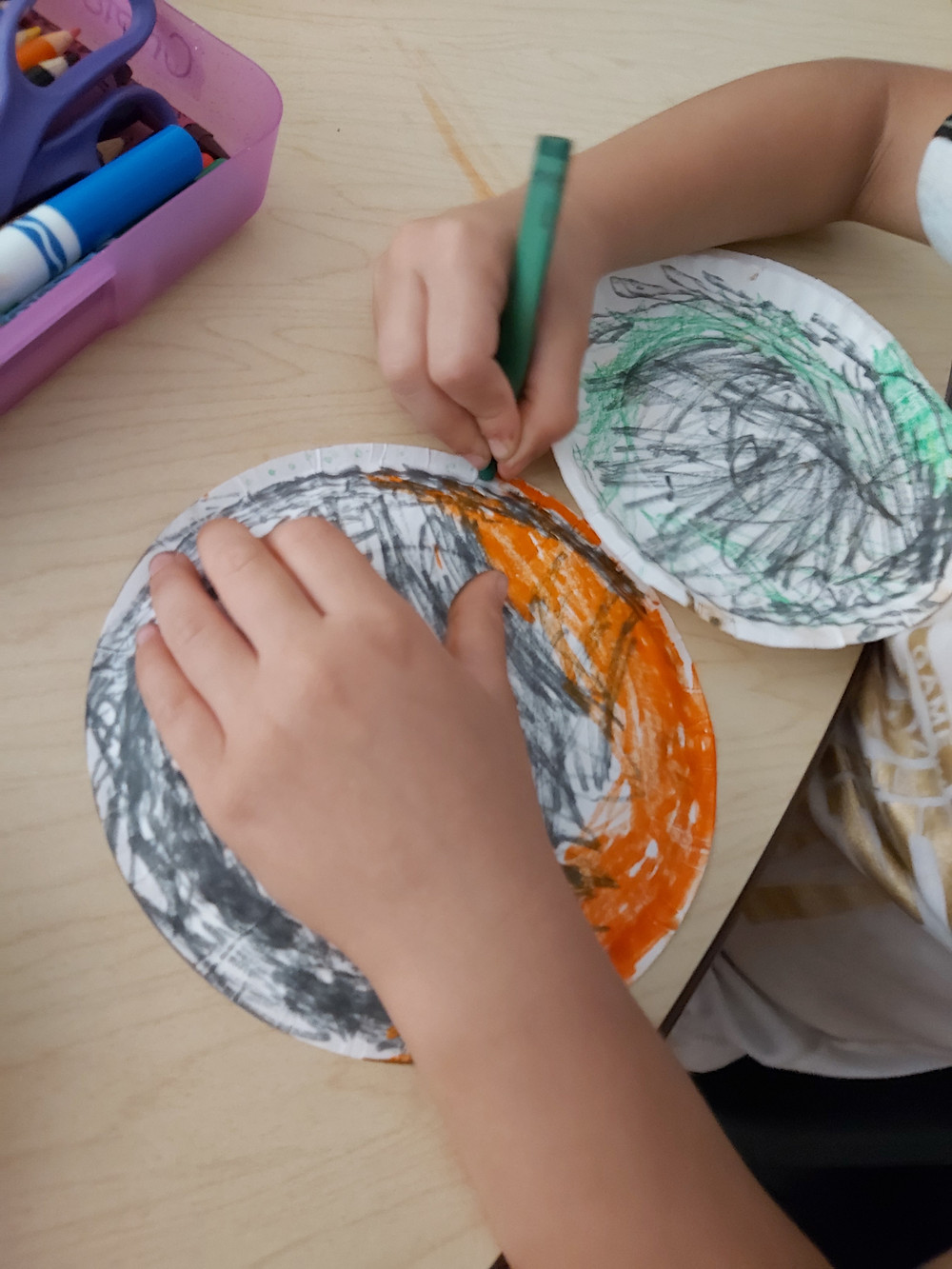 preschooler coloring two paper plates