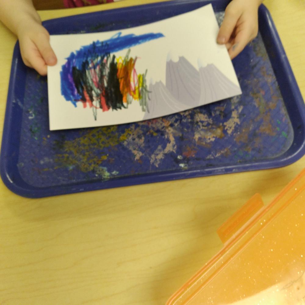 preschooler making winter postcard art on tray