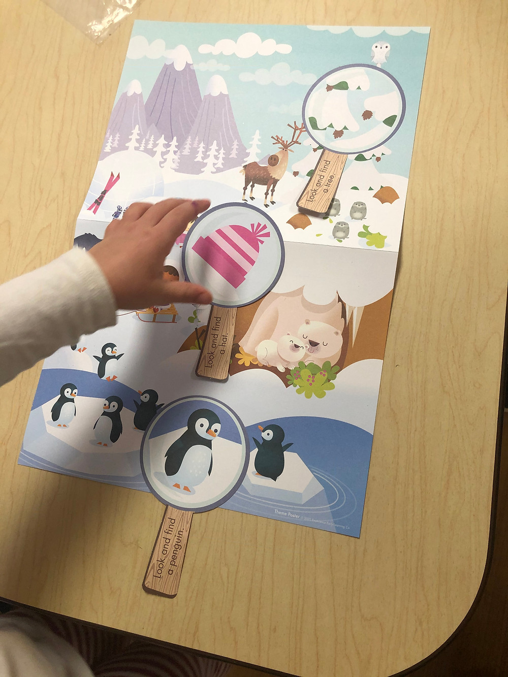 preschooler using pretend magnifying glass to explore monthly theme poster