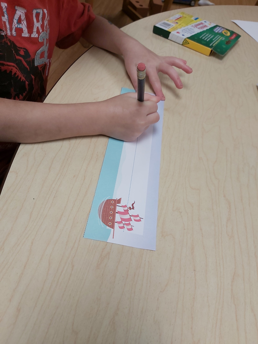 preschooler writing name on name tag