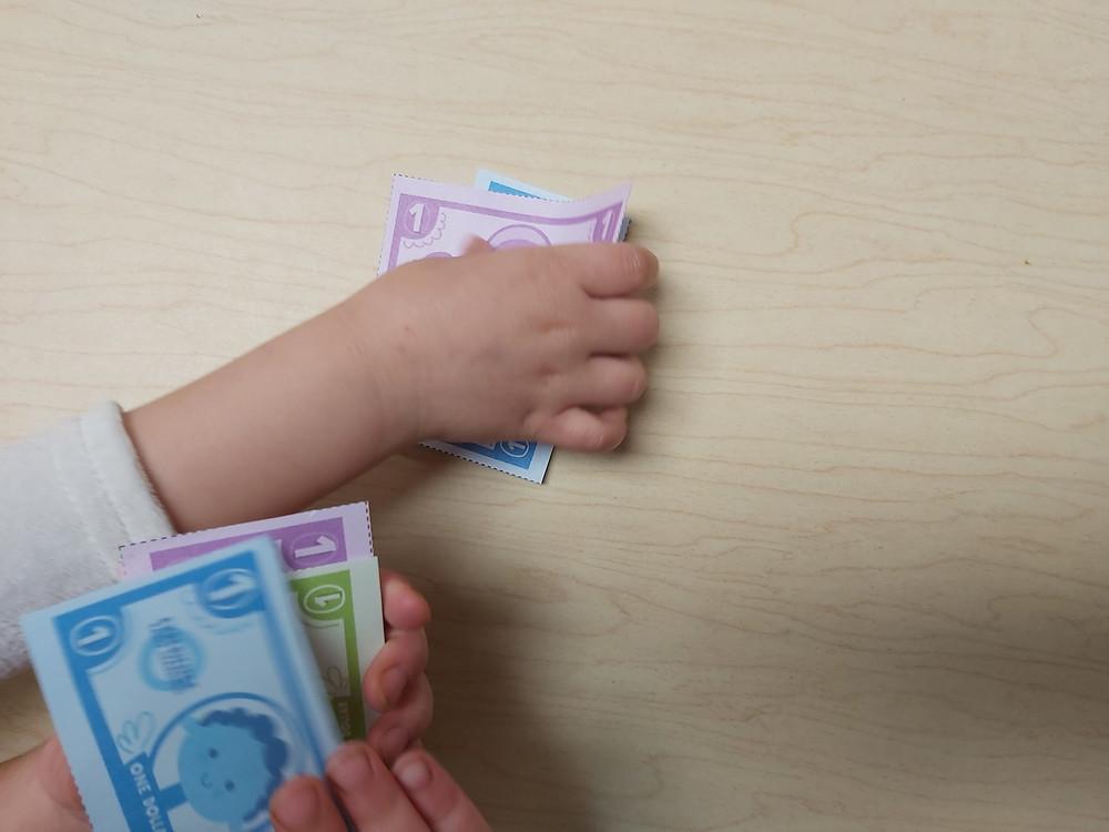 preschoolers exchanging pretend money