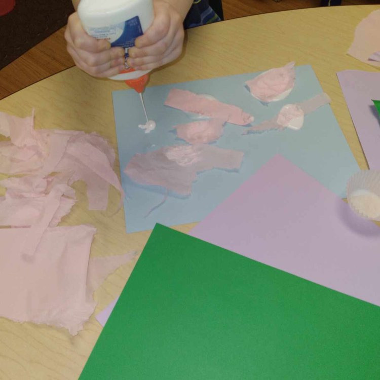 preschooler squeezing glue onto pond collage