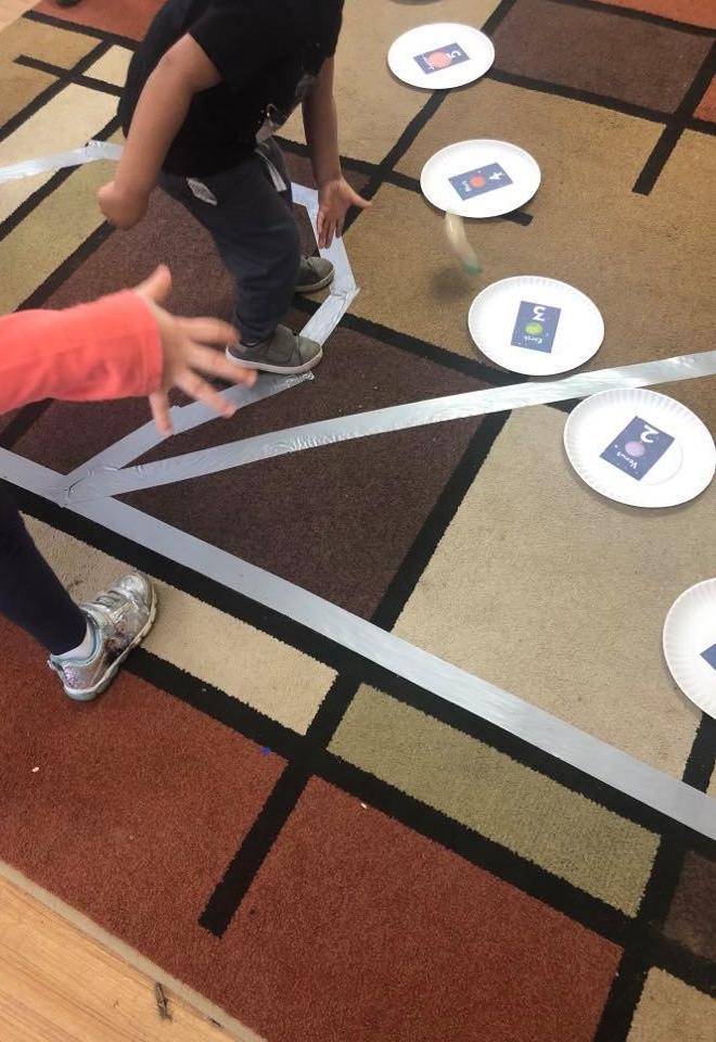 preschooler tossing pompom onto paper plate planet