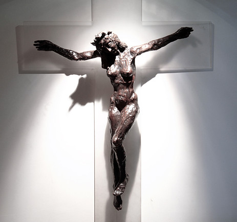 A bronze sculputre of a bare-breasted female form on the cross