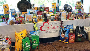 Table full of pet foods and supplies collected for animal shelters
