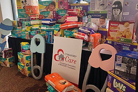 Table full of diapers and baby items collected for a diaper pantry