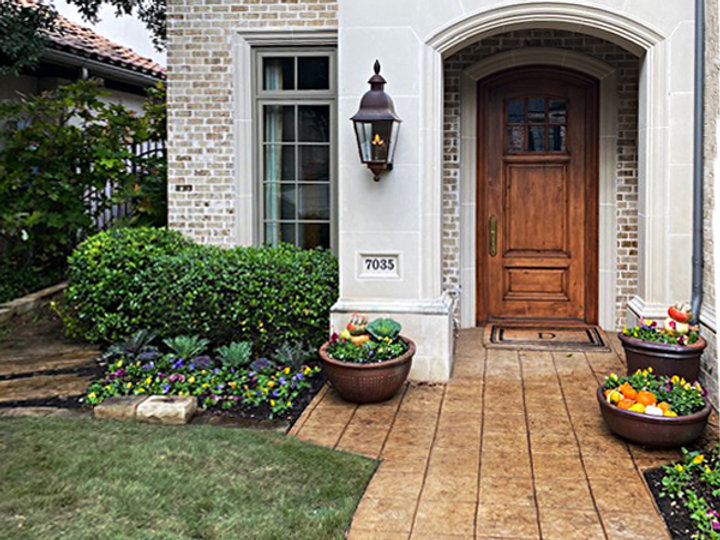 Fall planters with accent landscaping of pansies, kale, pumpkins and gourds provide a beautify reception to your home.