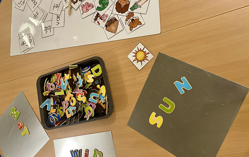 Magnet letters spelling sun,  other magnet letters and pictures.